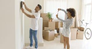 Hängende Bilder der jungen Paare in ihrem neuen Haus Stockfoto