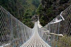 Hängende Brücke mit buddhistischen Gebetmarkierungsfahnen Lizenzfreie Stockfotografie