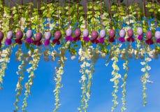Hängende bunte Ostereier und Blumendekor auf einem Hintergrund des blauen Himmels lizenzfreie stockfotografie