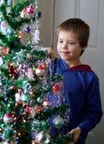 Hängende Eiszapfen des Jungen auf der Weihnachtsbaum-Feiertagsverzierung lizenzfreie stockfotos