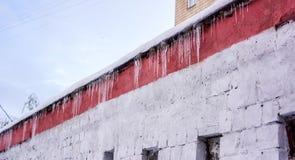 Hängende Eiszapfen des Winters auf dem Hausdach Lizenzfreie Stockfotos