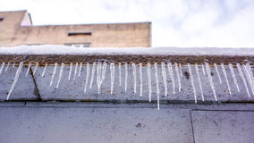 Hängende Eiszapfen des Winters auf dem Hausdach Zaun von Eiszapfen als Winterbeschaffenheit Lizenzfreies Stockfoto