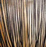 Hängende glänzende schwarze Spitzefranse auf einem Goldhintergrund lizenzfreie stockbilder