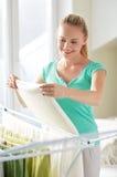 Hängende Kleidung der glücklichen Frau auf Trockner zu Hause lizenzfreie stockfotografie