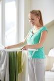 Hängende Kleidung der glücklichen Frau auf Trockner zu Hause lizenzfreie stockbilder