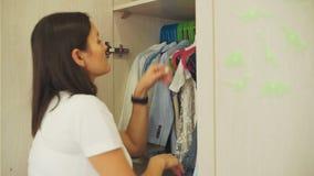 Hängende Kleidung der jungen Frau in einer Garderobe stock video footage