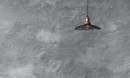 Hängende Lampen in der Dachbodenart gegen raue Wand mit grauem Zement Stockbild
