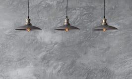 Hängende Lampen in der Dachbodenart gegen raue Wand mit grauem Zement Stockfoto