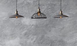 Hängende Lampen in der Dachbodenart gegen raue Wand mit grauem Zement Lizenzfreie Stockfotos
