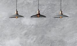 Hängende Lampen in der Dachbodenart gegen raue Wand mit grauem Zement Stockfotografie