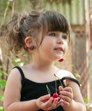 Hängende Paare des Kleinkindmädchens Kirschen auf ihrem Ohr Stockfotografie