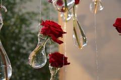 hängende rote Rosen in den Kristallvasen Lizenzfreie Stockfotografie