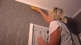 Hängende Tapete der blonden Frau, die unten es glatt macht stock footage