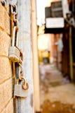 Hängende Verschlüsse und Ketten nähern sich Gasse zwischen Gebäuden lizenzfreie stockfotografie