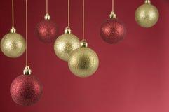 Hängende Weihnachtsdekorationen auf rotem Hintergrund Stockbild