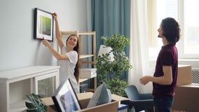 Hängendes Bild des Mannes und der Frau, das zu Hause Platz während der Verlegung wählt stock footage
