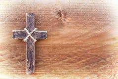 Hängendes hölzernes Kreuz auf altem hölzernem Hintergrund Stockfotografie