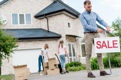 hängendes Verkaufszeichen des männlichen Grundstücksmaklers vor den verlagernden Leuten stockbilder