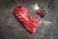 Hängendes zartes Steak auf einem Steinhintergrund mit Salz und Pfeffer - onglet Steak stockbild