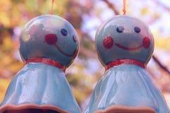 Hänger den övre bilden för slutet av keramiska dockor på linjen trädgårdbakgrund royaltyfri foto