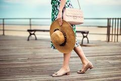 Hänger löst den bärande sommarklänningen för den ursnygga sexiga kvinnan, skor, rosa färger och att rymma hatten och gå på kustst Arkivfoto