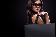 Hänger löst hållande grå färger för shoppingkvinna isolerat på mörk bakgrund i svart fredag ferie Arkivfoto
