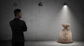 Hänger löst skuggade blickar för en affärsman på pengar anseende i ljuset under industriella lampor Royaltyfria Bilder