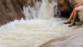 hänger trevliga flickans för closeupen ben över sjön vid vattenfallet parkerar in lager videofilmer