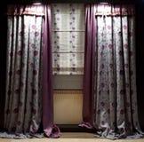hänger upp gardiner det lyxiga fönstret Fotografering för Bildbyråer