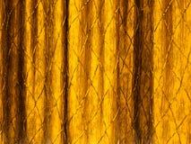 hänger upp gardiner guld Arkivfoto