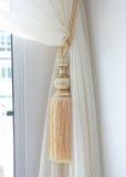 Hänger upp gardiner tofsen Arkivbild