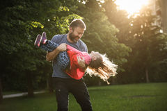 Hängiven fader som rotera hans dotter i cirklar arkivbild