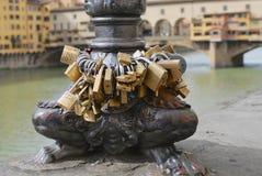 Hänglås låste på den Arno flodbanken med den Ponte Vecchio bron på bakgrunden i Florence, Italien Arkivfoto