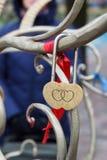 Hänglås med gravyr av två hjärtor på metallträd royaltyfria bilder