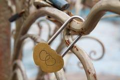 Hänglås med gravyr av två hjärtor på metallträd royaltyfri fotografi