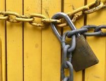 Hänglås och kedja i ljust gult staket royaltyfria foton