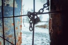 Hänglås och robust stålkedja som slås in runt om metallstänger på fönster royaltyfria bilder