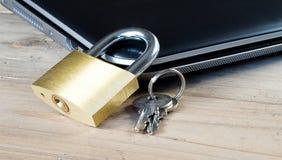 Hänglås och tangenter på den stängda anteckningsbokdatoren Royaltyfri Foto