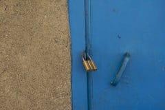 Hänglås på en blå dörr Arkivbild
