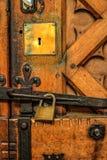 Hänglås på gammal ekdomkyrkadörr, med mässings- och järnmonteringar royaltyfri foto