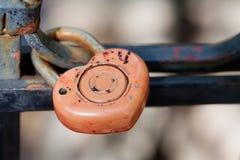 Hänglås på järnstaketet Rött lås, retro design makrosikt, mjuk fokus Symbolisk bild för förälskelsehjärta Fotografering för Bildbyråer