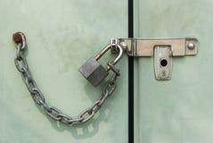 Hänglås som kedjas fast och låsas på dörr Arkivfoton