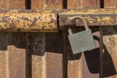 Hänglås som stänger den rostiga metalldörren royaltyfri fotografi