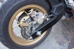 Hänglåssäkerhetslås som blockerar motorcykelhjulet på gata, a Arkivfoto
