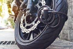 Hänglåssäkerhetslås som blockerar motorcykelhjulet på gatan, anti--stöld system Arkivbilder
