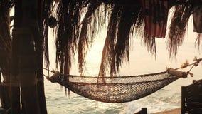 Hängmatta som hänger på palmträdet för att koppla av på stranden på havsbakgrund stock video