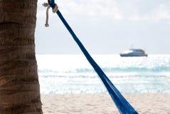 Hängmatta, strand och yacht. Royaltyfri Bild