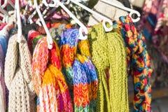 Hängning för många stucken scarves på hängaren Royaltyfri Foto