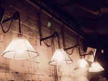 Hängning för tappningbelysninglampa framme av cementtegelstenväggen på vinden arkivbild