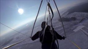 Hängning-glidflygplanet flyger i den soliga himlen över dentäckte ängen stock video
